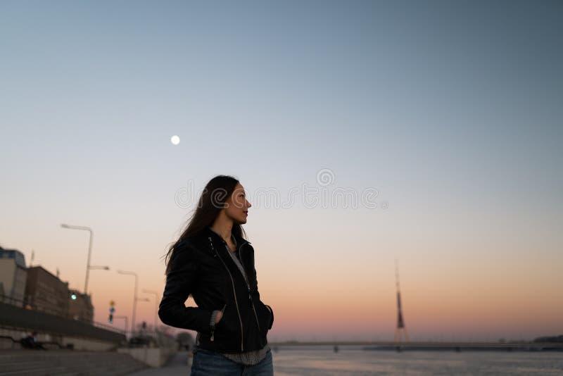 Młoda kobieta cieszy się zmierzchu spacer wzdłuż rzecznego Daugava z widokiem nad jasnym niebieskim niebem obrazy stock