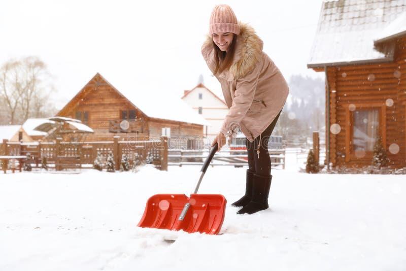 Młoda kobieta czyści śnieg z łopatą blisko jej domu obraz royalty free