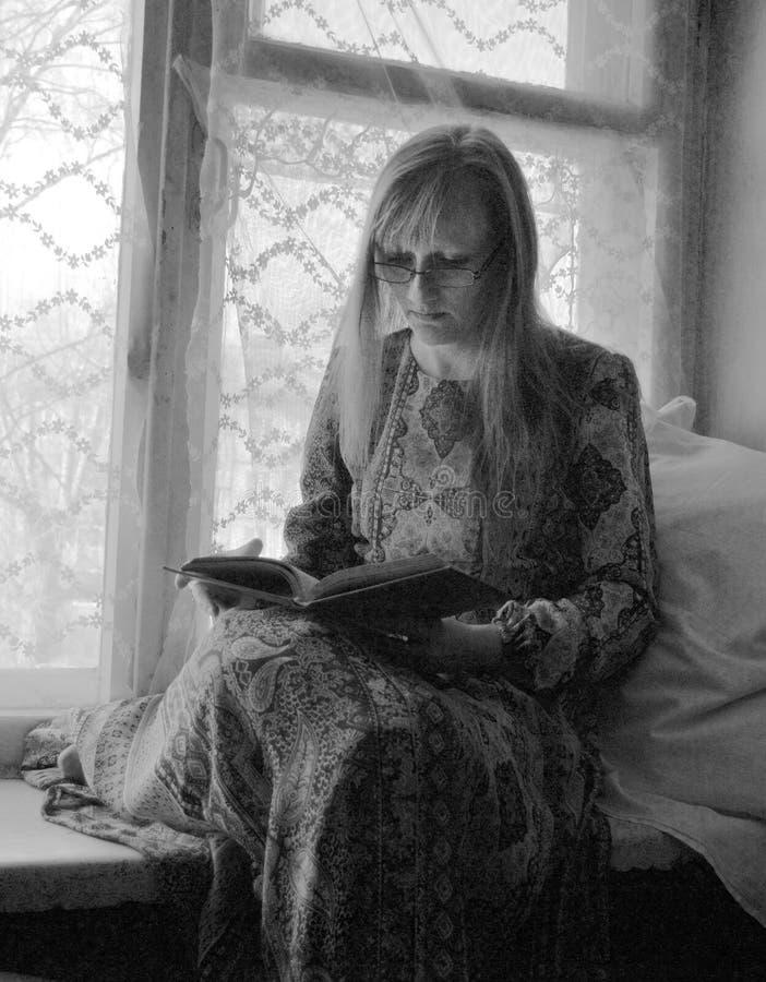 Młoda kobieta czyta książkę podczas gdy siedzący na okno obraz stock