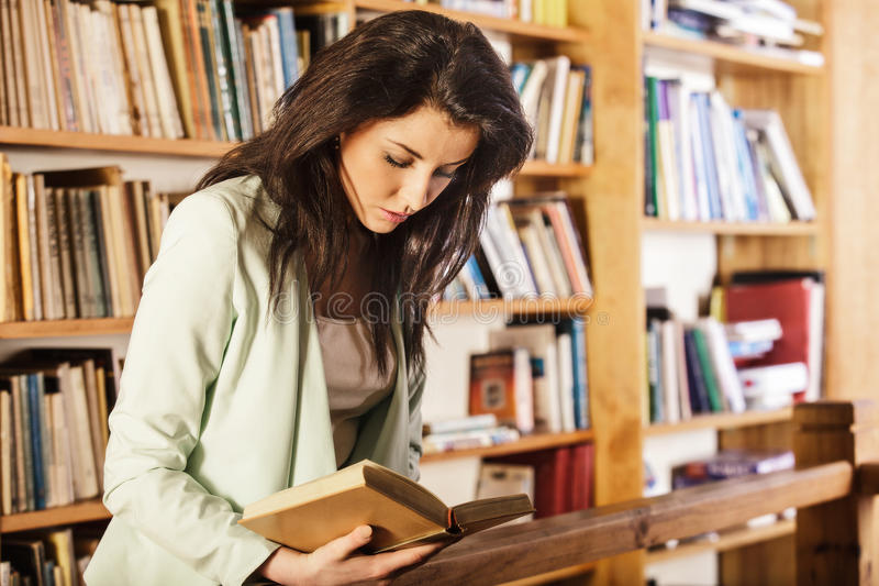 Młoda kobieta czyta książkę przed półka na książki zdjęcia royalty free