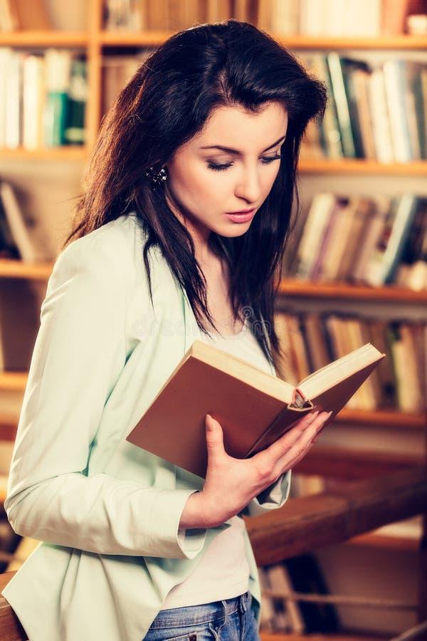 Młoda kobieta czyta książkę przed półka na książki zdjęcia stock