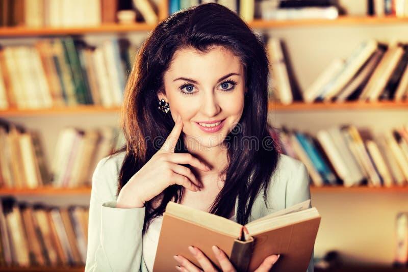 Młoda kobieta czyta książkę przed półka na książki obraz stock