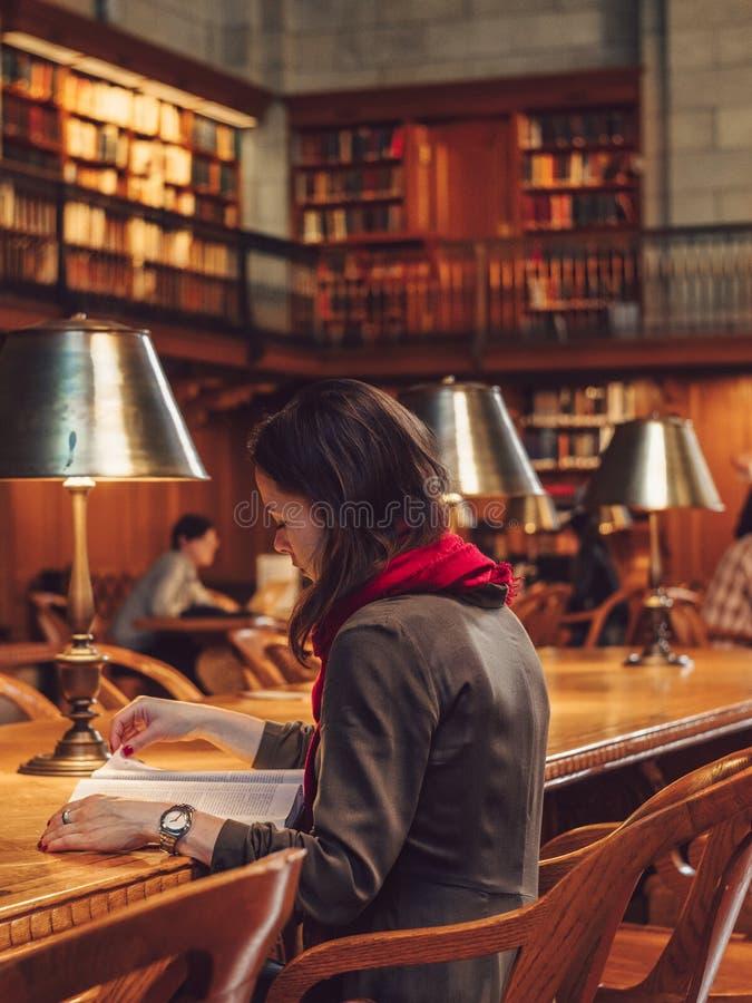 Młoda kobieta czyta książkę w bibliotece fotografia stock