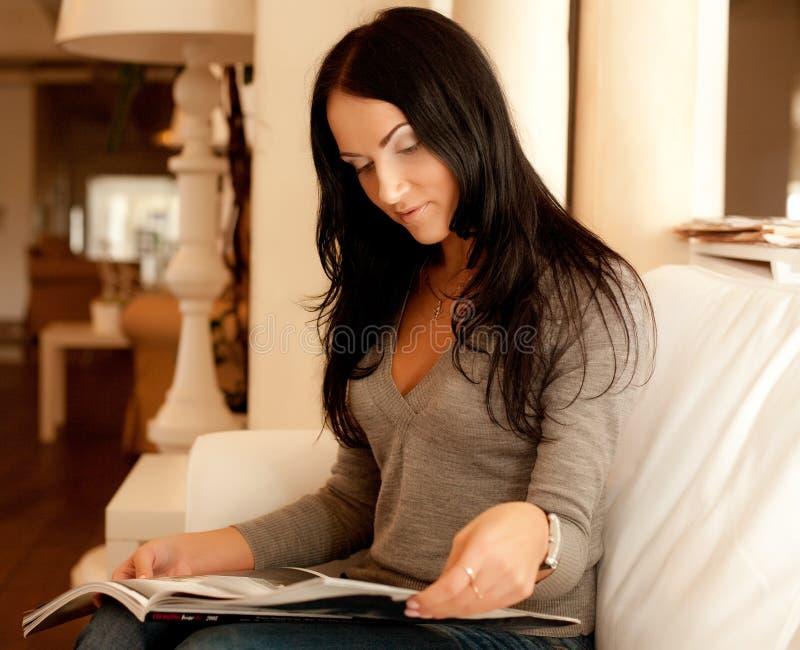 Młoda kobieta czytelniczy magazyn w domu zdjęcia stock