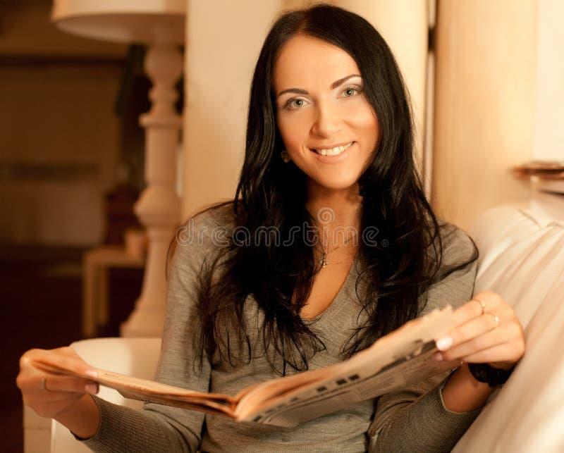 Młoda kobieta czytelniczy magazyn w domu zdjęcie royalty free
