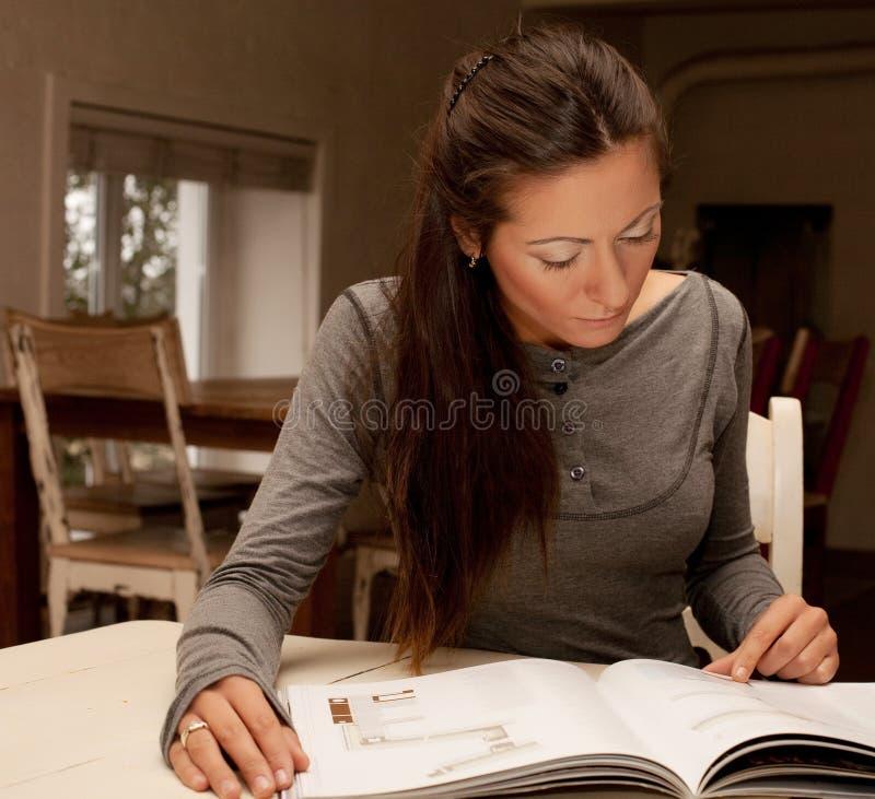 Młoda kobieta czytelniczy magazyn w domu fotografia stock