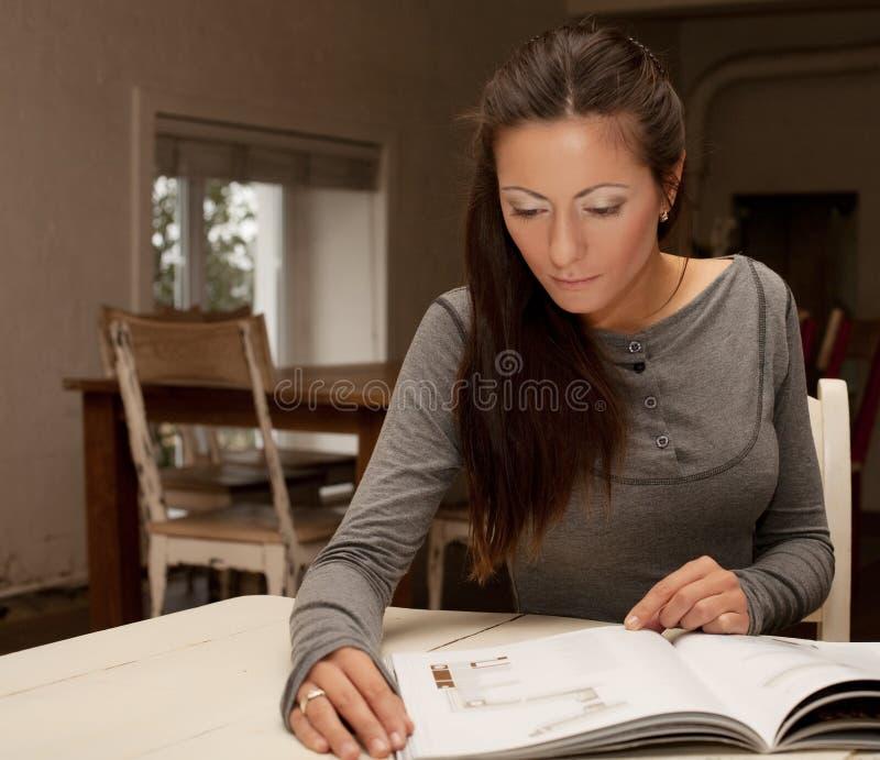 Młoda kobieta czytelniczy magazyn w domu obrazy stock
