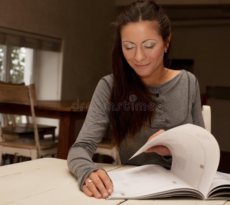 Młoda kobieta czytelniczy magazyn w domu zdjęcie stock