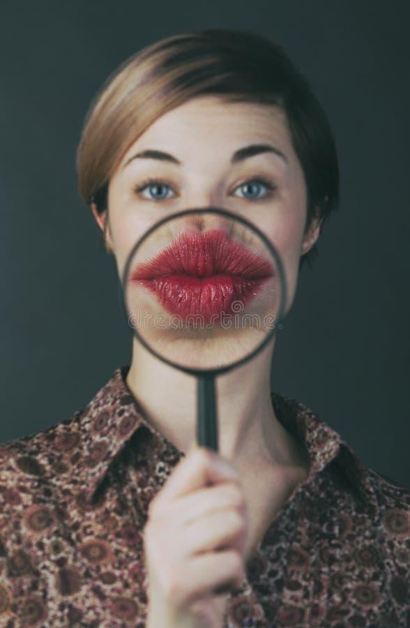 Młoda kobieta daje buziakowi przez powiększać - szkło obrazy royalty free