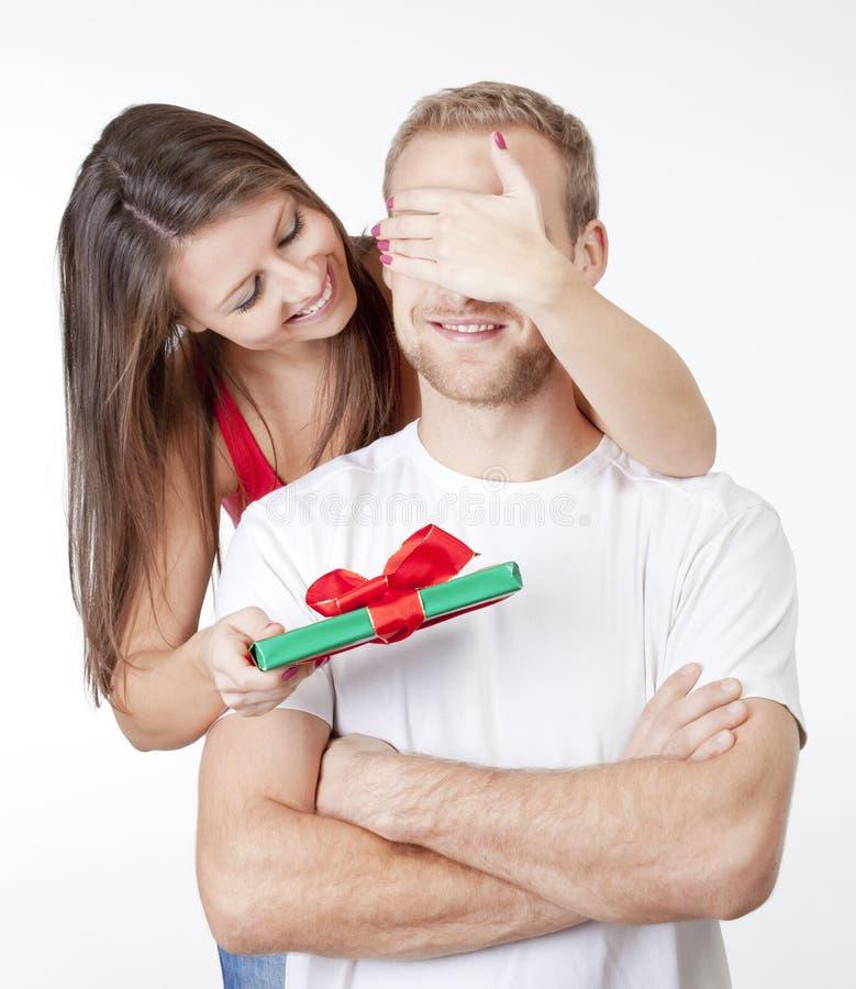 Młoda kobieta daje niespodziance teraźniejszej jej chłopak zdjęcie stock