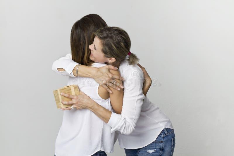 Młoda kobieta daje prezentowi jej przyjaciel Uśmiechać się dwa kobiet scenę fotografia stock