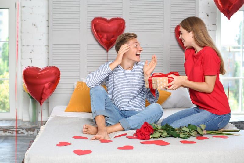 Młoda kobieta daje teraźniejszości jej ukochany chłopak w domu fotografia stock