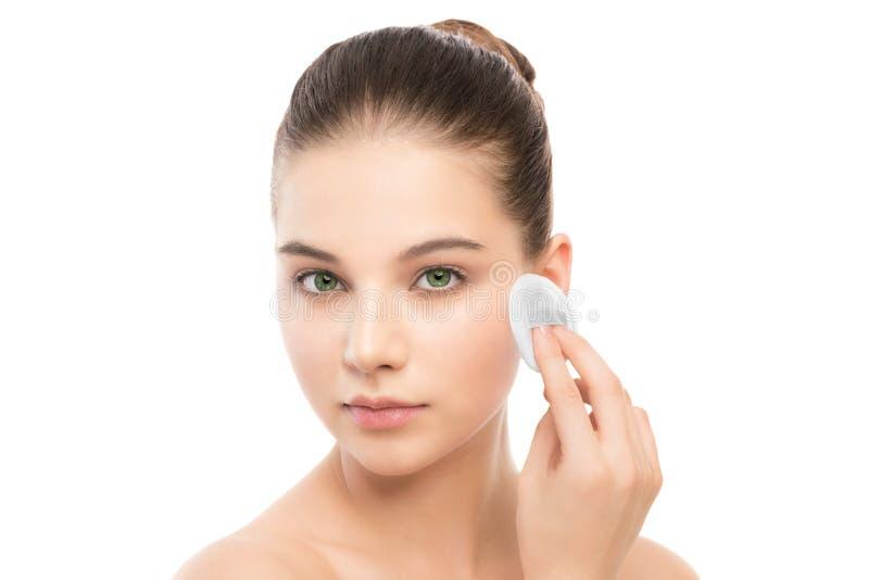 Młoda kobieta dba dla twarzy skóry Czyści perfect świeża skóra używać bawełnianego ochraniacza odosobniony zdjęcia stock