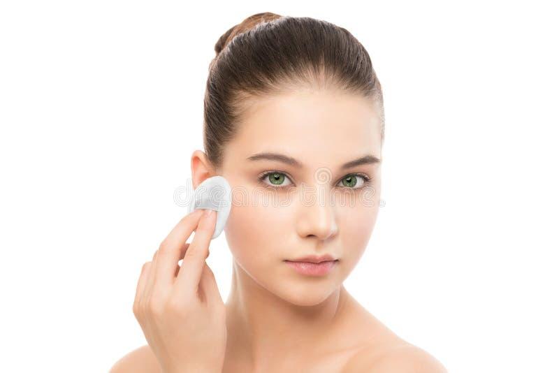 Młoda kobieta dba dla twarzy skóry Czyści perfect świeża skóra używać bawełnianego ochraniacza odosobniony fotografia royalty free