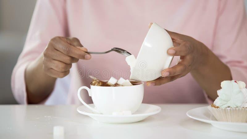 Młoda kobieta dodaje zbyt dużo cukieru w herbacianej filiżance, niezdrowy styl życia, cukrzyce zdjęcia stock