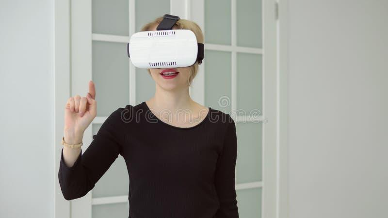 Młoda kobieta dostaje doświadczenie używać VR słuchawki szkła rzeczywistość wirtualna dużo gestykuluje ręki w domu obraz stock