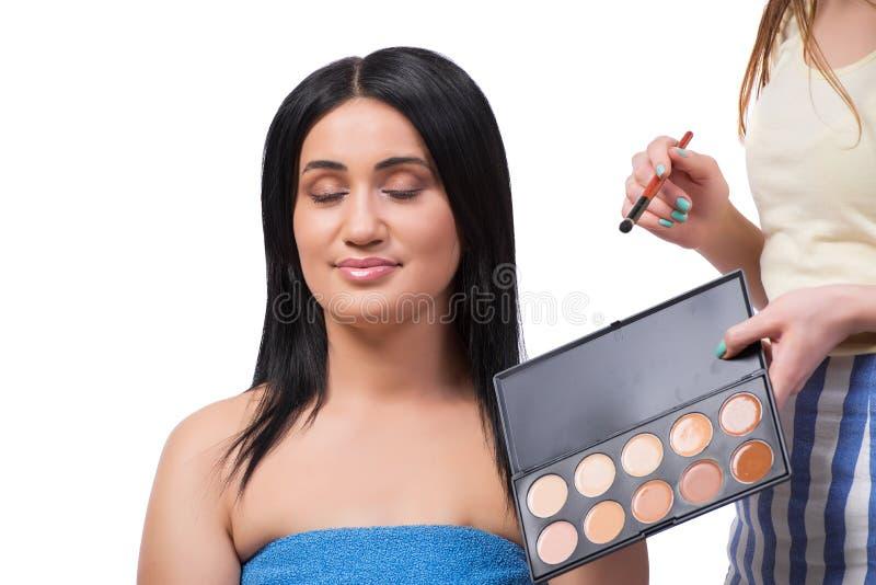 Młoda kobieta dostaje makijaż na bielu zdjęcie stock