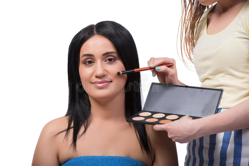 Młoda kobieta dostaje makijaż odizolowywający na bielu fotografia stock