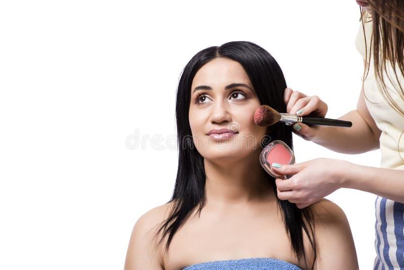 Młoda kobieta dostaje makijaż odizolowywający na bielu zdjęcia stock
