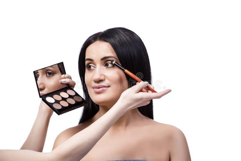 Młoda kobieta dostaje makijaż odizolowywający na bielu obraz stock