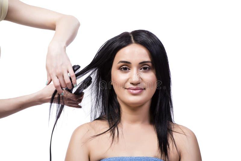 Młoda kobieta dostaje włosianego straightner odizolowywający na bielu fotografia stock