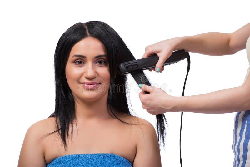 Młoda kobieta dostaje włosianego straightner odizolowywający na bielu zdjęcia royalty free