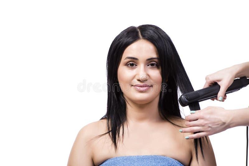 Młoda kobieta dostaje włosianego straightner odizolowywający na bielu obraz royalty free