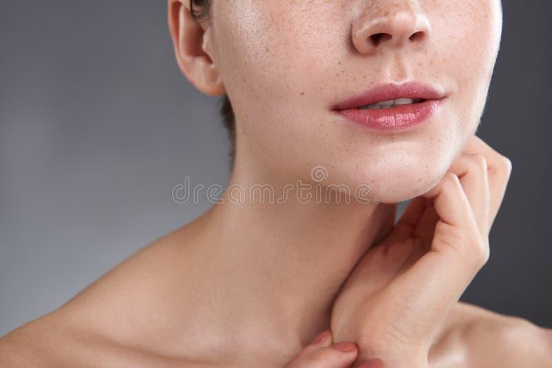 Młoda kobieta dotyka jej szyję z pięknymi różowymi wargami obrazy stock