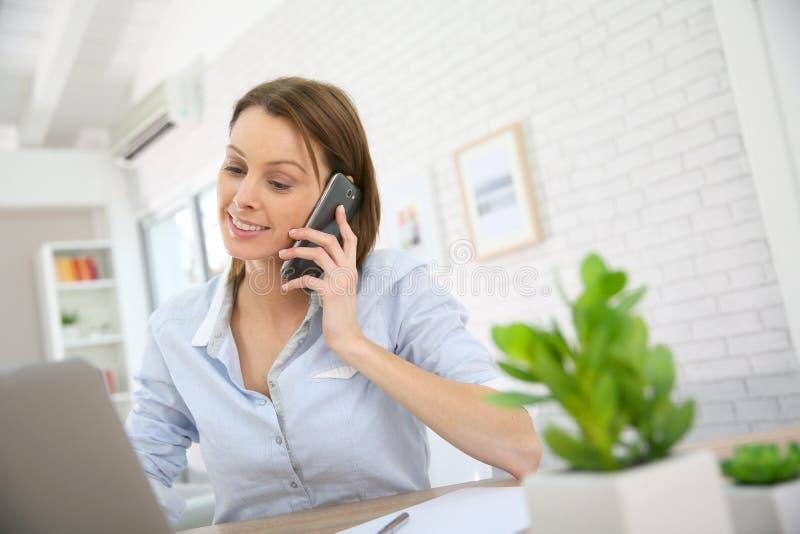 Młoda kobieta dyskutuje na telefonie przy biurem obraz stock