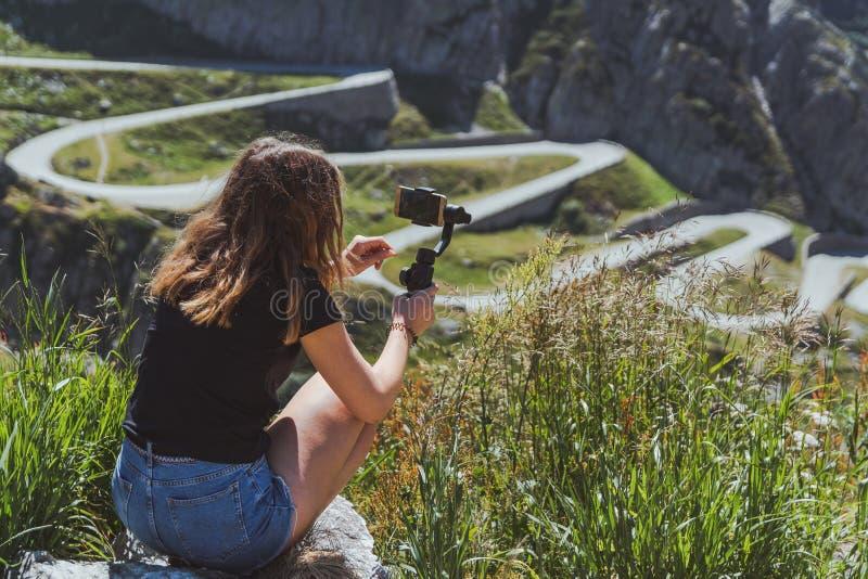 Młoda kobieta filmuje tremolo drogę w San gotthard używać smartphone i gimbal zdjęcia royalty free