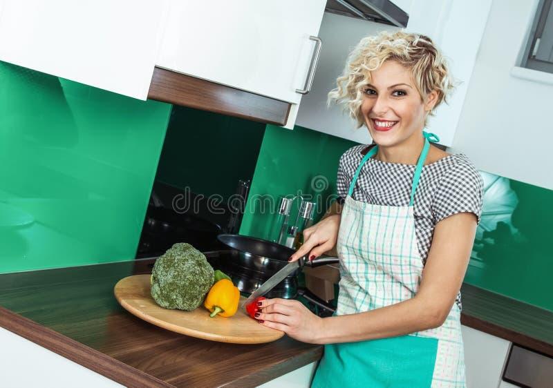 Młoda kobieta gotuje zdrowego jedzenie w domu zdjęcie stock