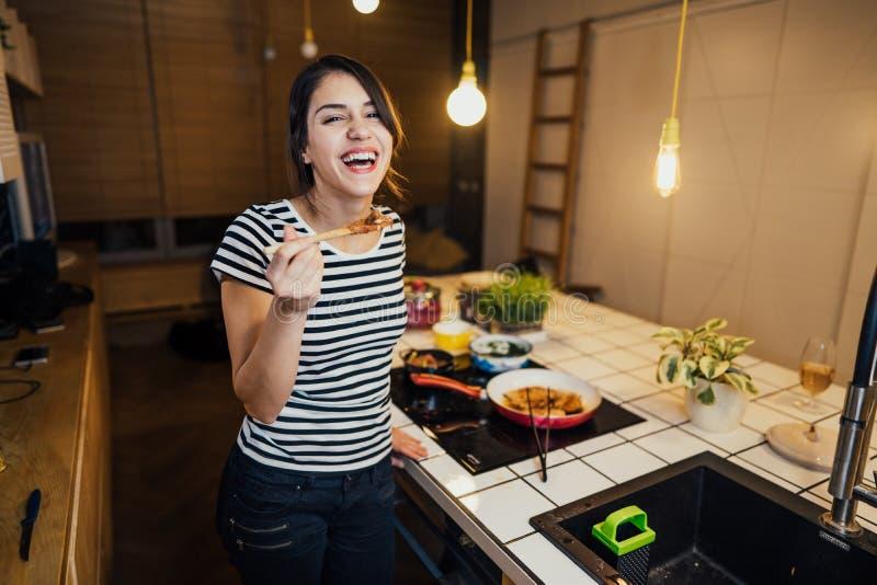 Młoda kobieta gotuje zdrowego posiłek w domowej kuchni Robić gościowi restauracji stoi bezczynnie indukcji hob na kuchennej wyspi obrazy stock