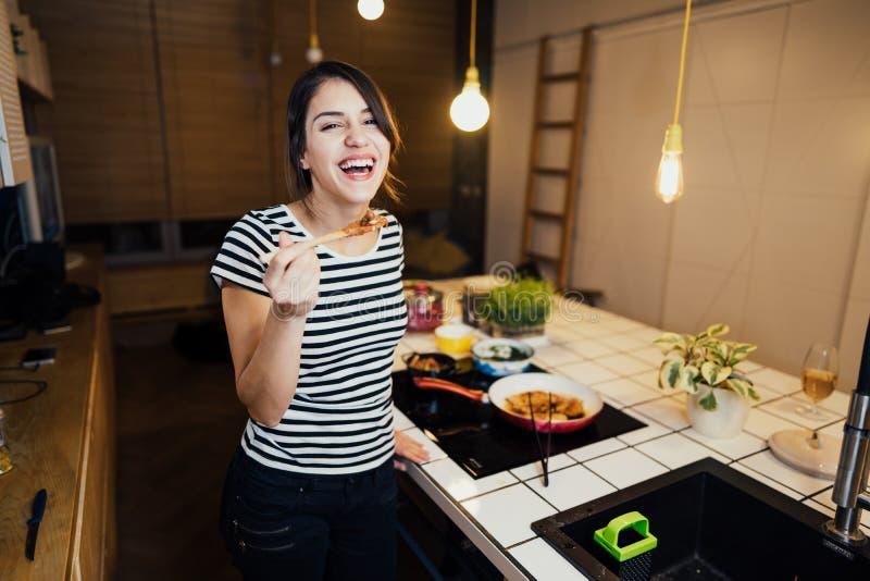 Młoda kobieta gotuje zdrowego posiłek w domowej kuchni Robić gościowi restauracji stoi bezczynnie indukcji hob na kuchennej wyspi zdjęcie royalty free