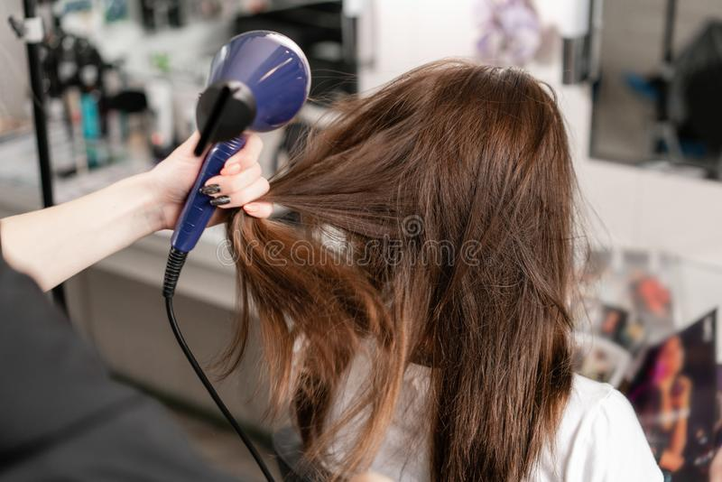 Młoda kobieta i fryzjer z fan robi gorącemu tytułowaniu przy włosianym salonem obraz stock