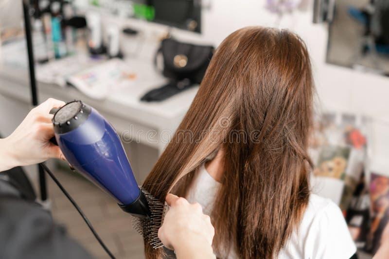 Młoda kobieta i fryzjer z fan robi gorącemu tytułowaniu przy włosianym salonem fotografia stock