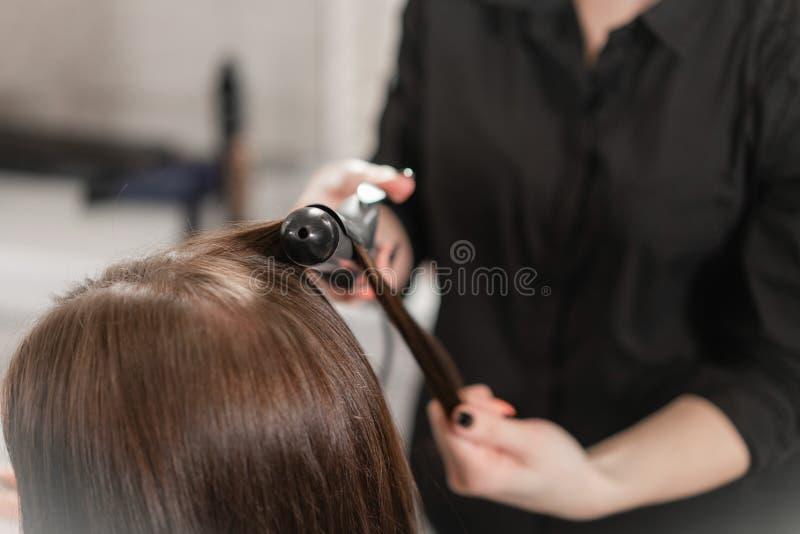 Młoda kobieta i fryzjer z fan robi gorącemu tytułowaniu przy włosianym salonem obrazy stock