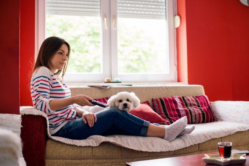 Młoda kobieta i jej zwierzę domowe na kanapie zdjęcia royalty free
