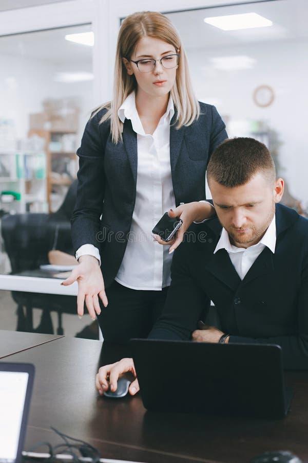 Młoda kobieta i mężczyzna dyskutujemy pracę przy stołem w biurze obrazy royalty free
