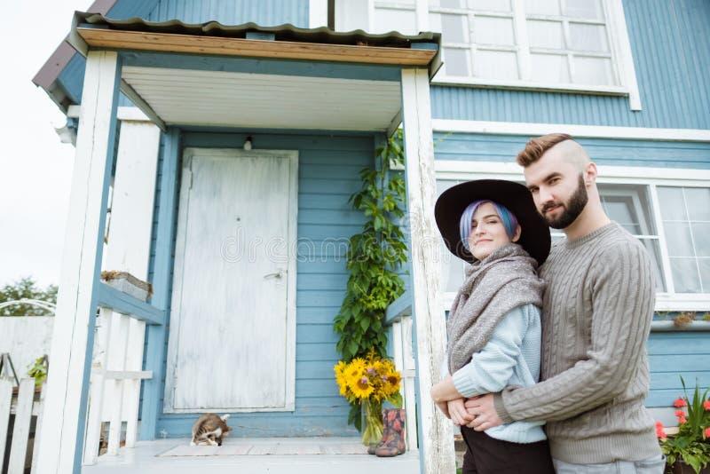 Młoda kobieta i mężczyzna, rodzina, siedzi na ganeczku wioska dom z baniami obrazy stock