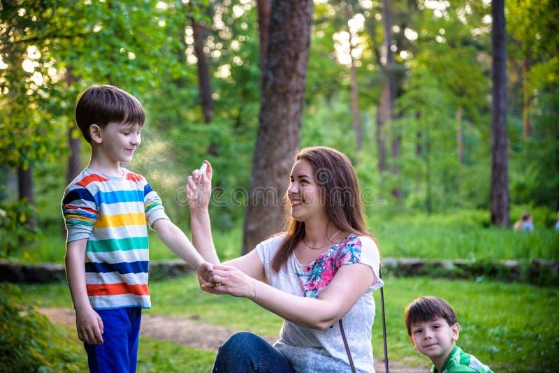 Młoda kobieta insekta macierzysty stosuje repellent jej dwa syn przed lasowej podwyżki pięknym letnim dniem lub wieczór chronieni zdjęcie royalty free