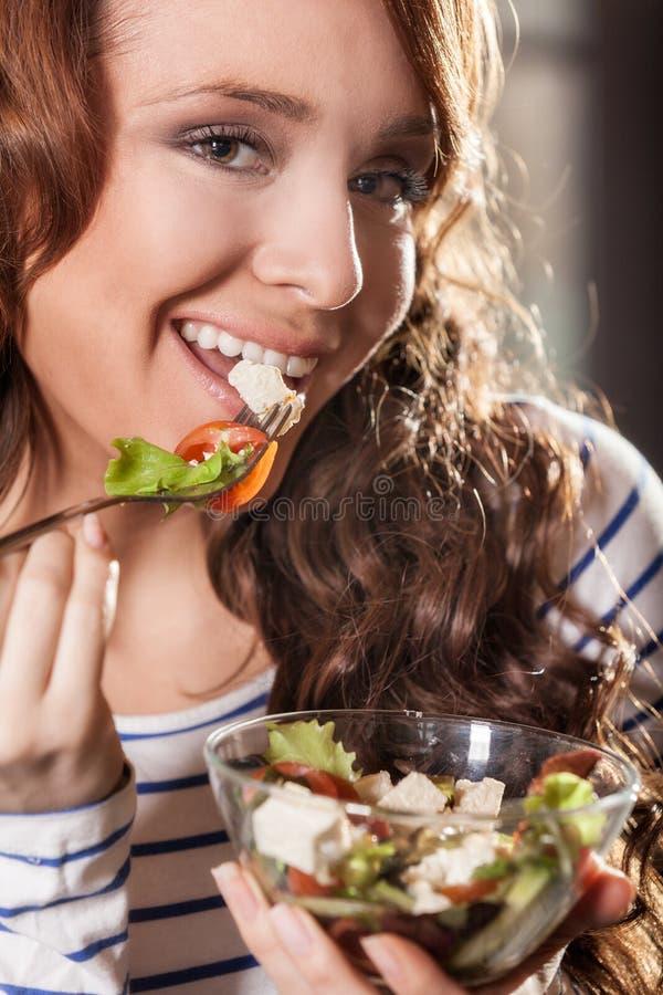 Młoda kobieta je świeżego warzywa sałatki zdjęcia stock