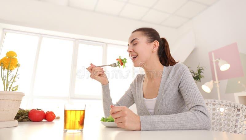 Młoda kobieta je świeżej sałatki w domu poj?cia zdrowe jedzenie fotografia royalty free