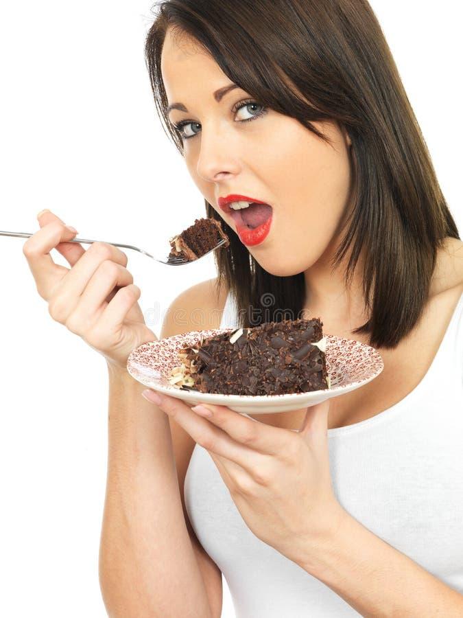 Młoda kobieta je czekoladowego tort zdjęcia stock