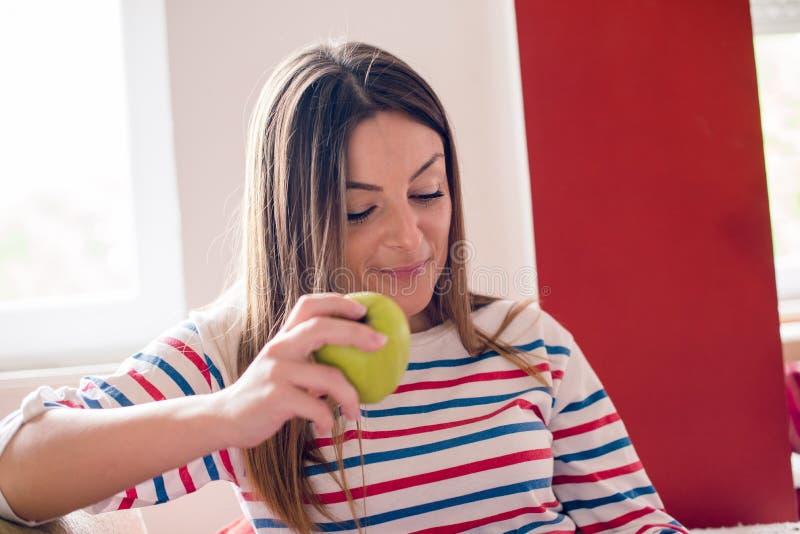 Młoda kobieta je jabłka i czytelniczego magazynu na kanapie obrazy stock
