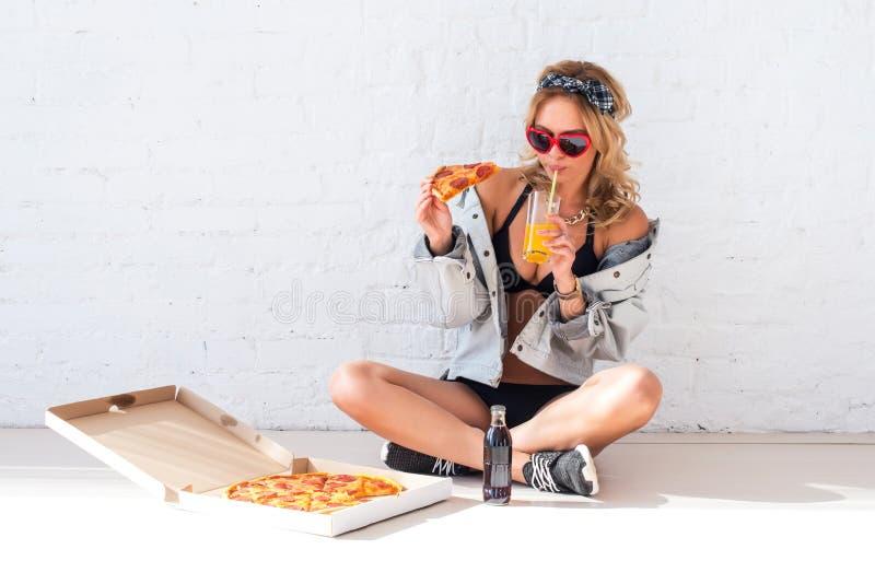 Młoda kobieta je kawałek pije soku obsiadanie na podłoga jest ubranym okulary przeciwsłonecznych pizza zdjęcie stock
