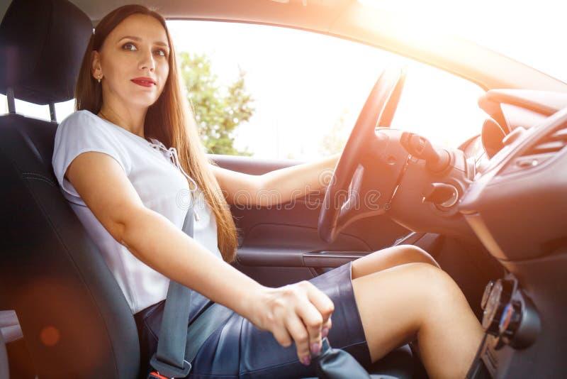 Młoda kobieta jedzie samochód na drodze zdjęcie stock