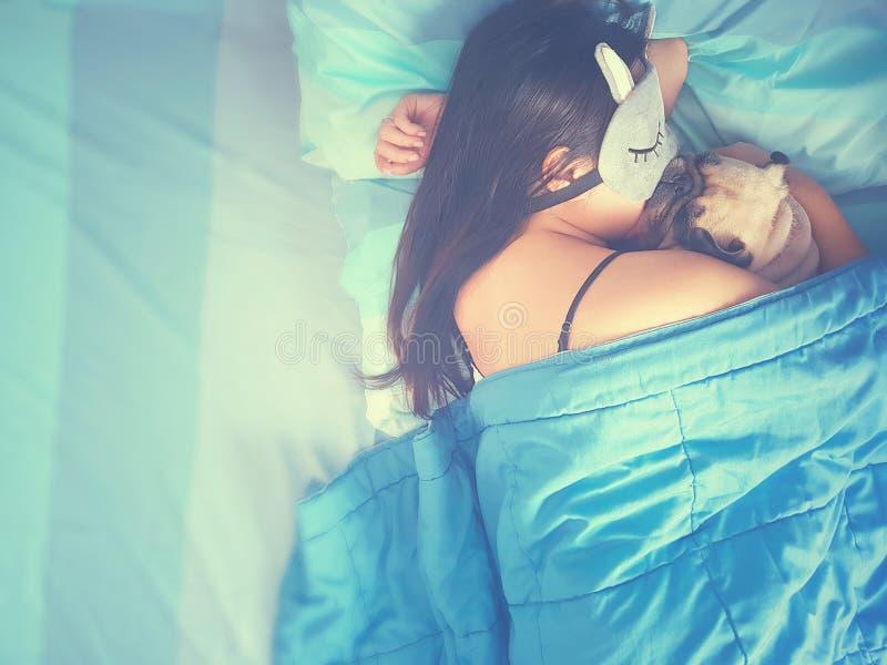 Młoda kobieta jest kłamająca i śpiąca z mopsa psa szczeniakiem w łóżku drzemka obrazy royalty free