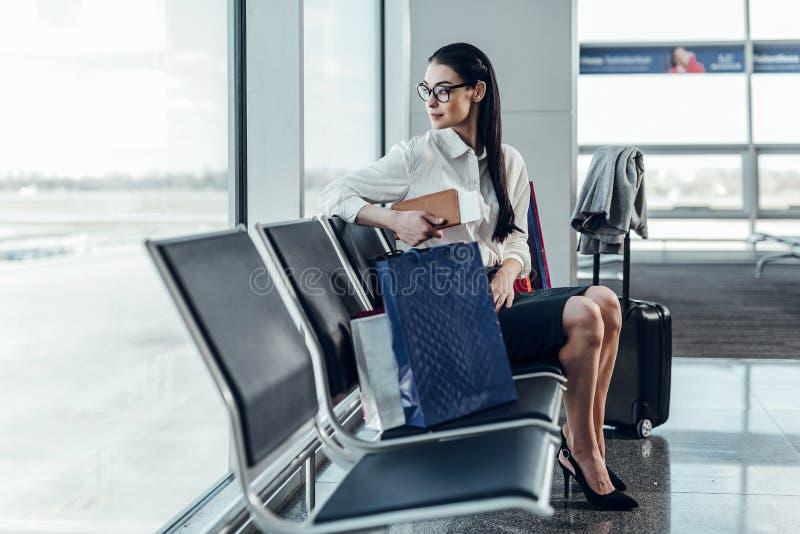 Młoda kobieta jest relaksująca w holu przed lotem zdjęcia stock