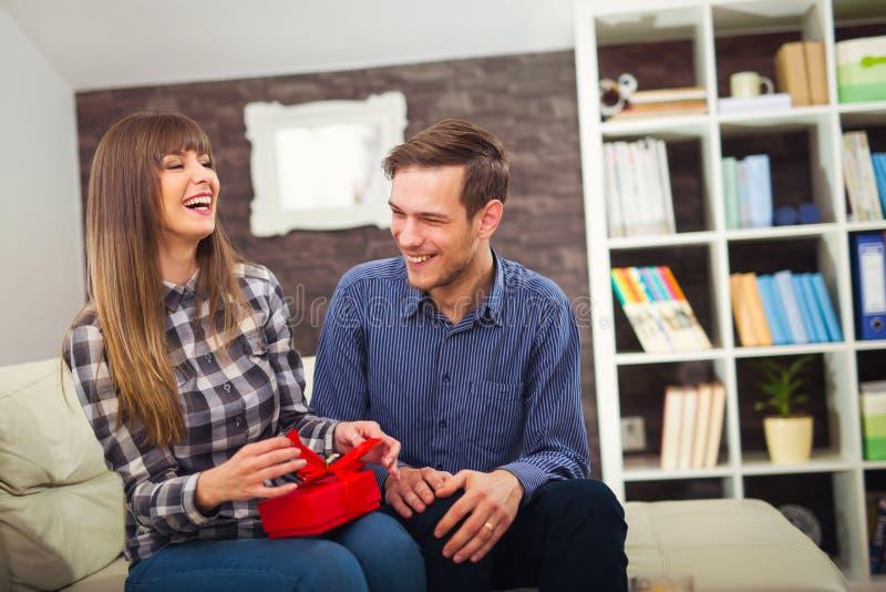 Młoda kobieta jest szczęśliwa i zdziwiona z prezentem od jej męża, obraz stock