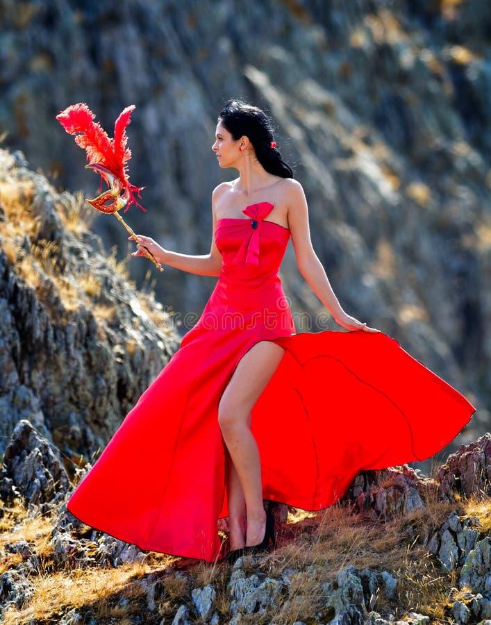 Młoda kobieta jest ubranym długą czerwieni suknię, maskę i obrazy stock